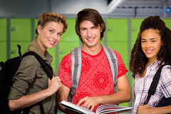 Composite image of college students reading book in library. College students reading book in library against locker room Royalty Free Stock Images