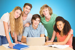 Composite image of college students using laptop in library. College students using laptop in library against blue background with vignette Stock Photo