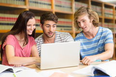 Composite image of college students using laptop in library. College students using laptop in library against close up of a bookshelf Royalty Free Stock Image