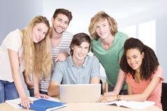 Composite image of college students using laptop in library. College students using laptop in library against modern hallway Stock Images