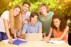 Composite image of college students using laptop in library. College students using laptop in library against trees and meadow in the park Stock Photos
