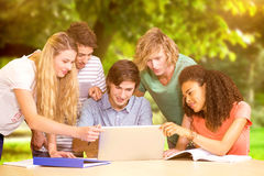 Composite image of college students using laptop in library Stock Photo