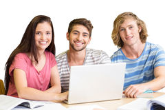 Composite image of college students using laptop in library. College students using laptop in library against white background with vignette Royalty Free Stock Image