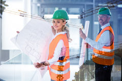 Composite image of collegues holding plans on building construction site Stock Photography