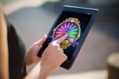 Composite image of colorful wheel of fortune on mobile display. Colorful wheel of fortune on mobile display against businesswoman using digital tablet Stock Image