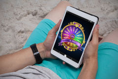 Composite image of colorful wheel of fortune on mobile display. Colorful wheel of fortune on mobile display against man using digital tablet on the beach Royalty Free Stock Photography