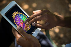 Composite image of colorful wheel of fortune on mobile display. Colorful wheel of fortune on mobile display against man using tablet computer Stock Images