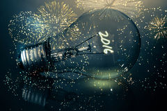 Composite image of colourful fireworks exploding on black background. Colourful fireworks exploding on black background against 2016 light bulb Royalty Free Stock Photos