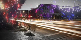 Composite image of colourful fireworks exploding on black background. Colourful fireworks exploding on black background against light trails on city street Stock Photo