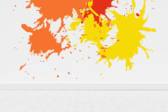 Composite image of colourful paint splashes. Colourful paint splashes against blue wall by hardwood floor Stock Images