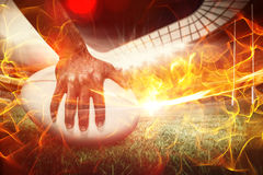 Composite image of composite image of close-up of sports player holding ball 3d. Composite image of close-up of sports player holding ball against ball of fire Stock Images