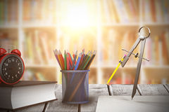 Composite image of composite image of drawing compass with pencil. Composite image of drawing compass with pencil against shelf of books Stock Images