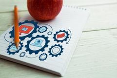 Composite image of composite image of education icons on gears. Composite image of education icons on gears against view of an apple and notepad royalty free stock images
