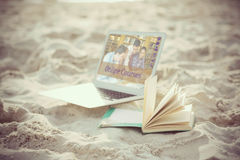 Composite image of composite image of online courses. Composite image of online courses against open book and laptop on sand at beach Royalty Free Stock Images