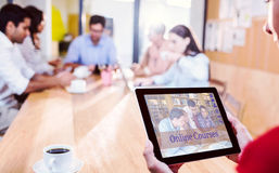 Composite image of composite image of online courses. Composite image of online courses against women holding digital tablet with colleagues in background Stock Photography