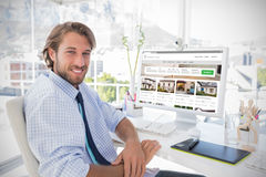 Composite image of composite image of property web site. Composite image of property web site against smiling designer sitting at his desk Stock Photo