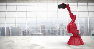 Composite image of composite image of red robot holding phone 3d. Composite image of red robot holding phone against modern room overlooking city 3d royalty free stock photos