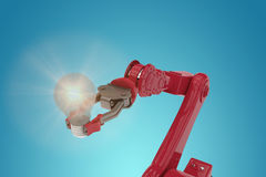 Composite image of composite image of red robotic arm holding light bulb 3d. Composite image of red robotic arm holding light bulb against blue vignette Stock Image