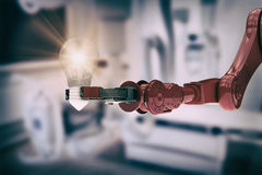 Composite image of composite image of robotic arm holding light bulb Stock Photos