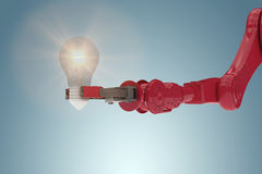 Composite image of composite image of robotic arm holding light bulb 3d. Composite image of robotic arm holding light bulb against grey vignette 3d Royalty Free Stock Images