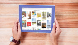 Composite image of composite image of website page. Composite image of website page against overhead of feminine hands using tablet Royalty Free Stock Image
