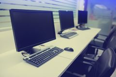 Composite image of computer in office or training room. The computer is on the table in a bright interior. white desk and black revolving chair with computer stock photo