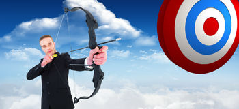 Composite image of concentrated businessman shooting a bow and arrow Stock Image