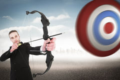 Composite image of concentrated businessman shooting a bow and arrow Royalty Free Stock Photo