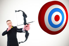 Composite image of concentrated businessman shooting a bow and arrow Stock Photo