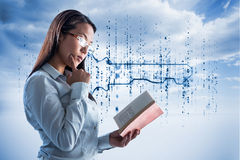 Composite image of concentrated businesswoman reading book. Concentrated businesswoman reading book against digital blue key Stock Photo