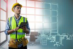 Composite image of concentrated construction worker with tablet. Concentrated Construction Worker With Tablet against interior of empty office Royalty Free Stock Image