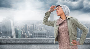 Composite image of concentrated young model in winter clothes watching around her Stock Image