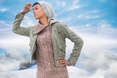 Composite image of concentrated young model in winter clothes watching around her Stock Images