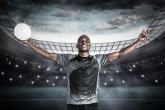 Composite image of confident athlete with arms raised holding rugby ball Royalty Free Stock Photography