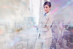 Composite image of confident businesswoman holding laptop. Confident businesswoman holding laptop against high angle view of city stock image