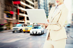 Composite image of confident businesswoman holding laptop. Confident businesswoman holding laptop against new york street royalty free stock photo