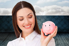 Composite image of confident businesswoman holding a piggybank Royalty Free Stock Images