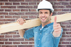 Composite image of confident carpenter carrying wooden plank Stock Photo