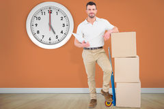 Composite image of confident delivery man with cardboard boxes Stock Photo