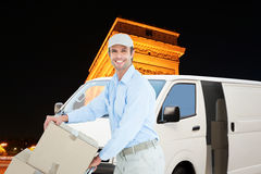 Composite image of confident delivery man pushing trolley of cardboard boxes Royalty Free Stock Images