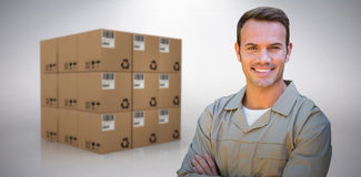 Composite image of confident delivery man standing with arms crossed Stock Images