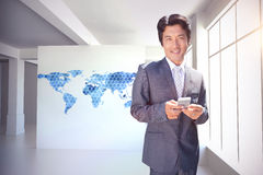 Composite image of confident estate agent standing at front door texting Stock Photo