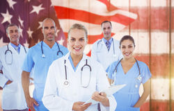 Composite image of confident female doctor with team over white background Royalty Free Stock Images