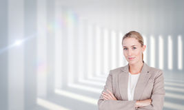 Composite image of confident female executive with folded arms Stock Photo