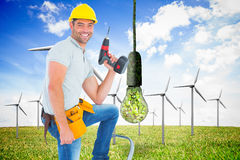 Composite image of confident handyman holding power drill while climbing ladder. Confident handyman holding power drill while climbing ladder against renewable Royalty Free Stock Images
