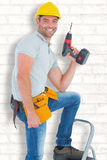 Composite image of confident handyman holding power drill while climbing ladder. Confident handyman holding power drill while climbing ladder against white wall Royalty Free Stock Photos