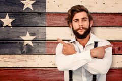 Composite image of confident hipster pointing sideways with arms crossed. Confident hipster pointing sideways with arms crossed against composite image of usa Stock Image