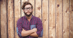 Composite image of confident hipster wearing eye glasses with arms crossed. Confident hipster wearing eye glasses with arms crossed against wooden planks stock photo