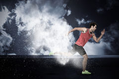 Composite image of confident male athlete running from starting blocks. Confident male athlete running from starting blocks against splashing of dust powder Stock Images