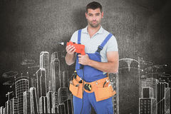 Composite image of confident male carpenter in overall holding drill machine Stock Image